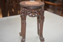 A small Chinese marble-inset carved hardwood vase stand, the circular top with beaded rim, on four