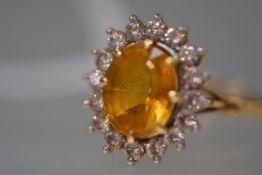 A golden beryl and diamond ring, the central mixed-cut oval beryl within a band of sixteen round