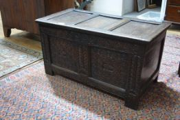 A small oak coffer, late 17th century, the triple panel hinged top above a pair of front panels