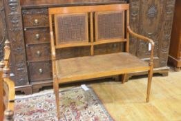 An Edwardian inlaid satinwood double chairback settee, the crest rail inlaid with ribbon-tied