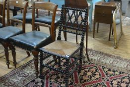 A Victorian ebonised bobbin-turned chair, with lozenge back splat, rush seat, the legs joined by
