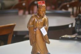 An Oriental carved, gilt and lacquered carving of a standing figure in formal robe holding a box.