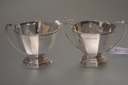 A George V cased silver sugar and cream, Hukin & Heath, Birmingham 1933, each of faceted oval