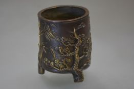 A Chinese patinated bronze brush pot, of cylindrical form, cast in relief with pine and bamboo,