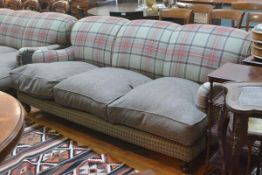 A three seater sofa, upholstered in a green tartan and tweed, with loose cushioned seat, raised on