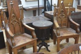 A striking pair of pitch pine Gothic Revival throne chairs, each back with triangular crest over