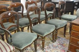 A set of eight Victorian mahogany balloon back dining chairs, each with scroll carved backsplat,