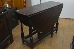 An 18th century oak gateleg dining table, with twin leaves, fitted with two frieze drawers, raised