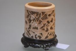 A Chinese tusk section ivory brush pot, Canton, 19th century, carved in relief with dragons