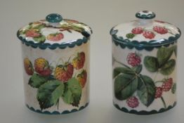 Two Wemyss Pottery preserve jars: each of cylindrical form with domed cover, one painted with