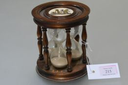 A rosewood triple hourglass timer, the three glasses within turned baluster spindles, inset to top