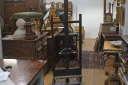 A large ebonised artist's easel, c. 1900, with adjustable top bar and deep base shelf, on a
