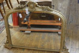A small Victorian gilt-composition overmantel mirror, the arched plate beneath a shield and floral