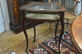 A late 19th century gilt-metal mounted mahogany vitrine table, the glazed cartouche shaped hinged