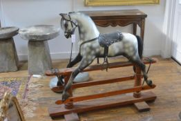 An early 20th century painted wooden rocking horse, possibly F.H. Ayres, dappled, with glass eyes,