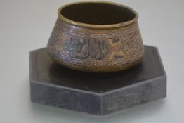 A 19th century brass bowl of Mamluk type, decorated with cartouches of calligraphy in mixed