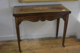 An Edwardian inlaid rosewood foldover card table, the rectangular swivelling top above a scroll