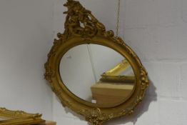 A late 19th century giltwood mirror, the oval plate within a conforming frame with putto surmount,