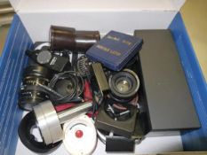 A box containing a collection of camera equipment to include light meters, filters and lenses