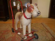 A vintage Tri-ang push-along fox terrier, c. 1960, the composition body with glass eyes and red