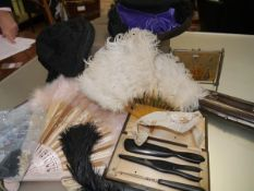 A group of lady's vintage accessories including two feather fans, a lace fan, a black bonnet,