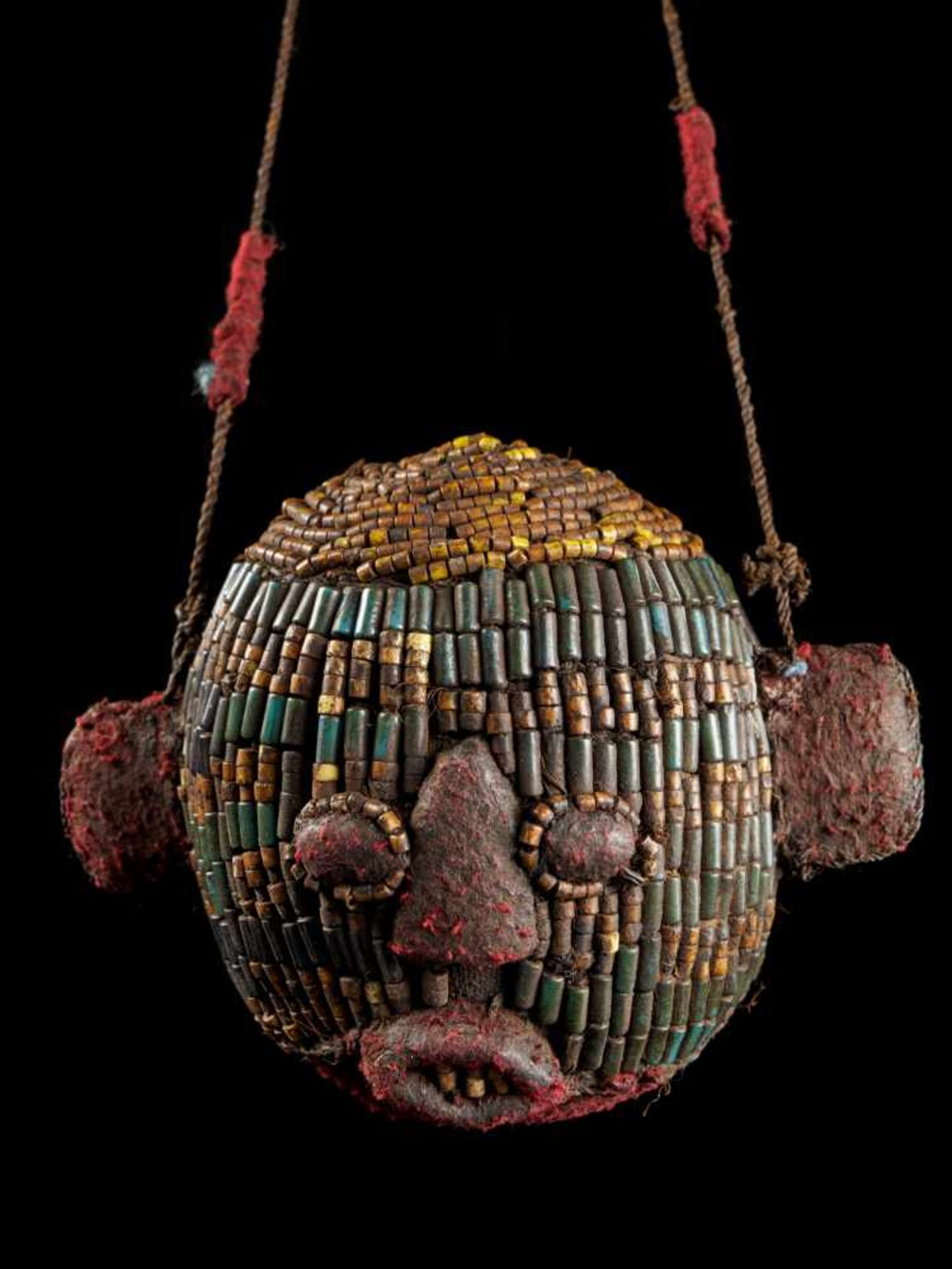 Beaded Ceremonial Trophy Head - Tribal ArtFashioned from wood, red cloth and blue and yellow glass