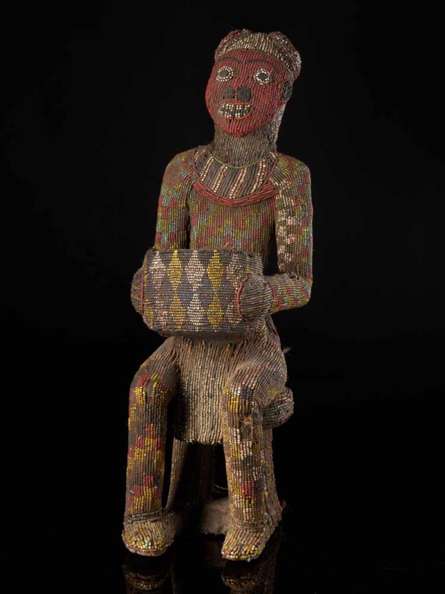 Beaded Figure Of Cupholder - Tribal ArtA beaded figure of a man sitting on a stool, holding a cup.