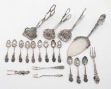 Tortenheber, drei Gebäckzangen, zwölf Mokkalöffel und vier Gäbelchen Silber. Reliefierte