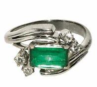 Ring 8 K WG. Der geschwungene Ringkopf besetzt mit einem Smaragd in Baguetteschliff, ca. 0,9 ct.,
