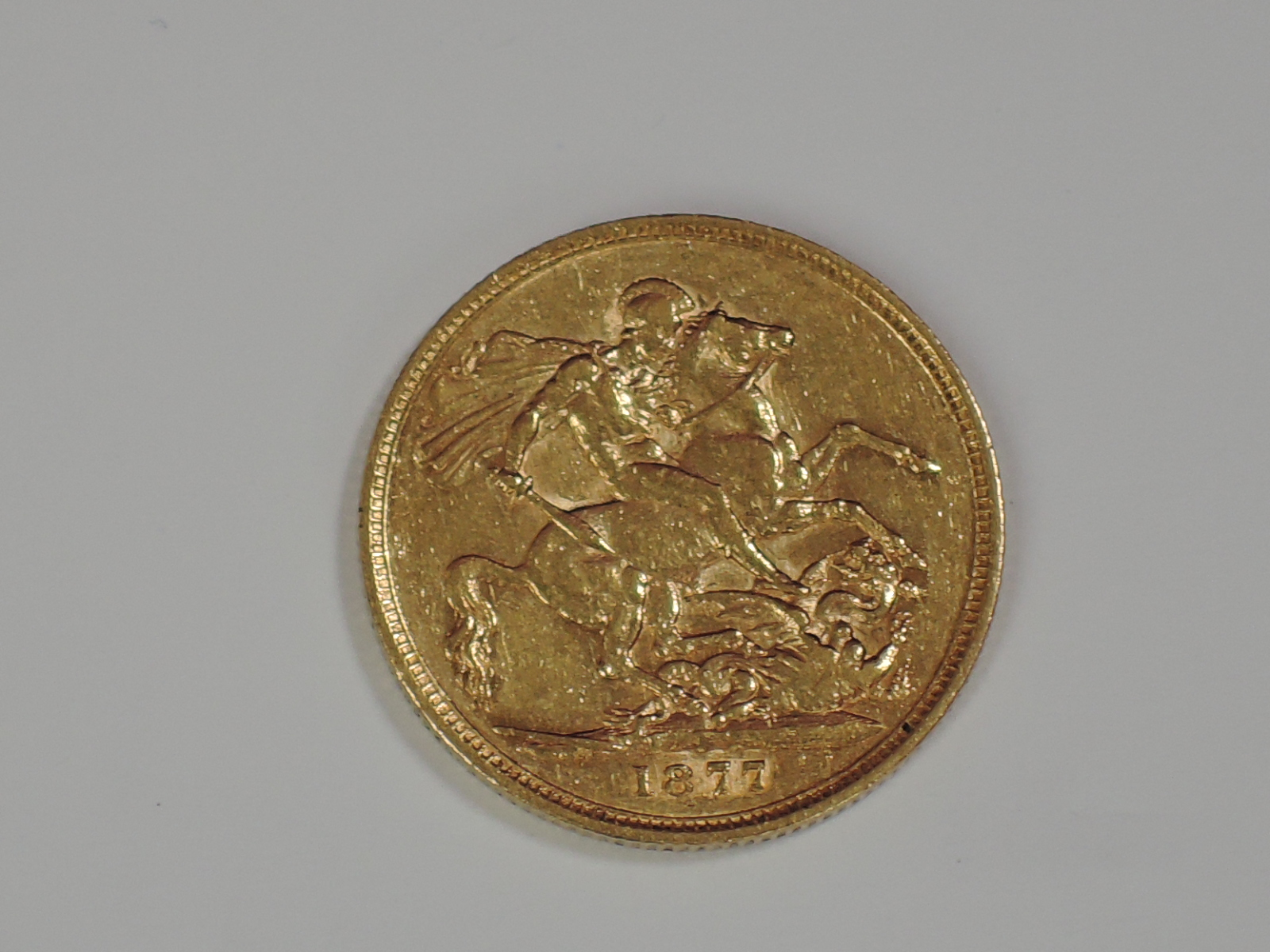 Lot 653 - A gold 1877 Great Britain Victoria, young head Sovereign coin, in plastic case, Melbourne Mint
