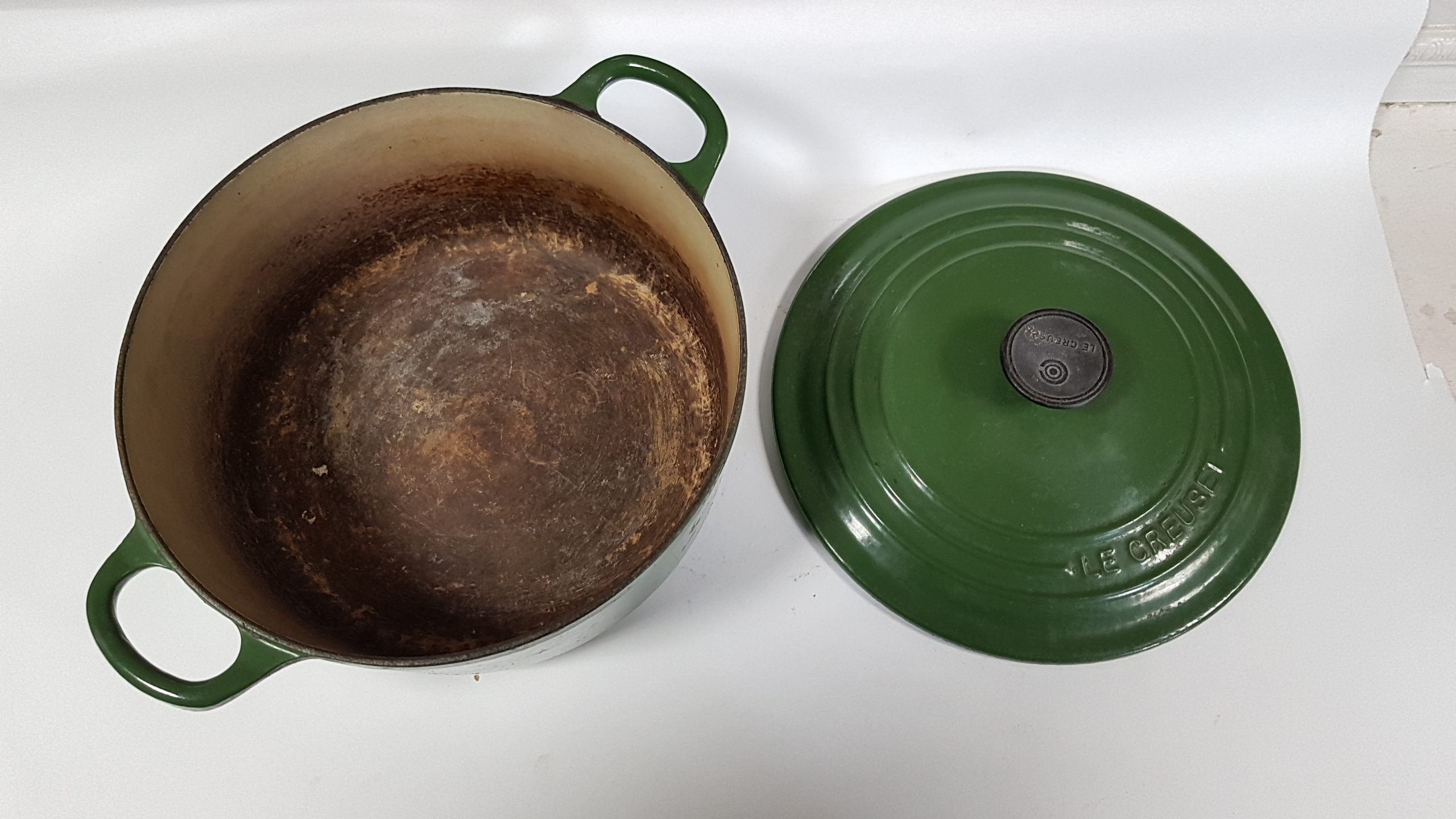 Lot 47 - A set of seven Le Creuset green enamelled cooking pots; & a black painted cast-iron saucepan pot