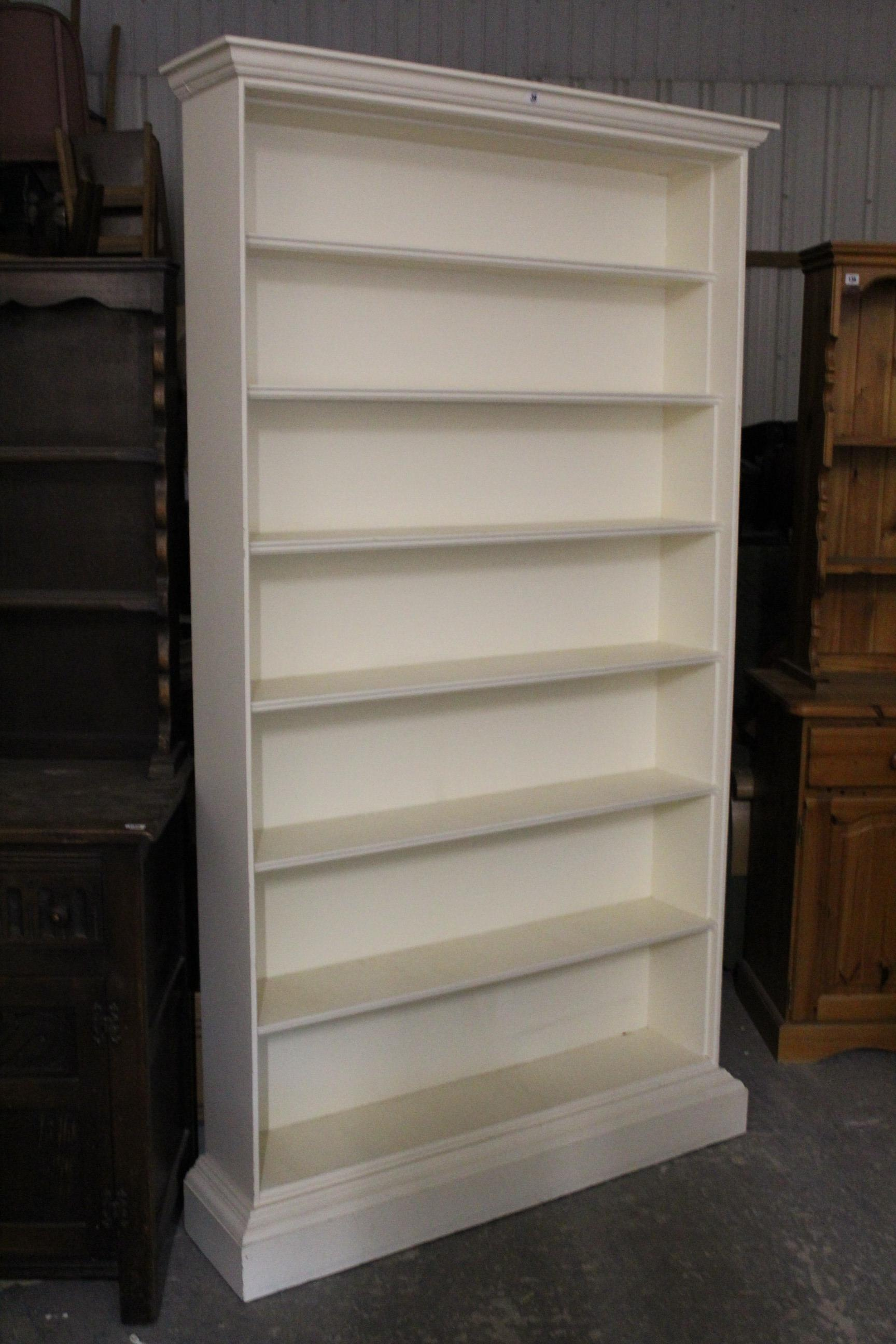 """Lot 39 - A white painted wooden tall standing seven-tier open bookcase on plinth base, 45"""" wide x 80½"""" high."""
