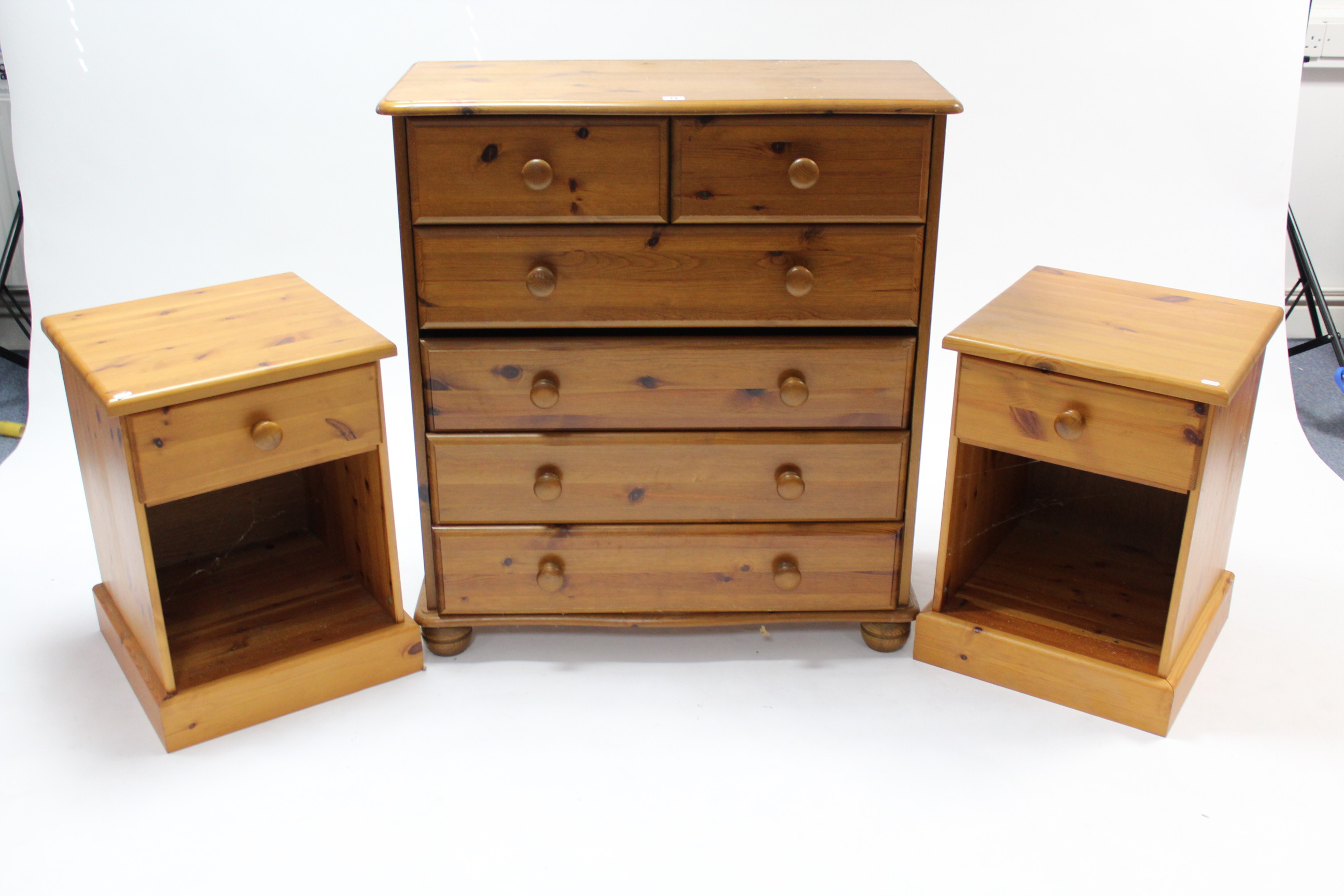 Lot 14 - A pine serpentine-front chest fitted two short & four long drawers with turned knob handles; & on