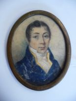 Lot 52 - An early 19thC oval head and shoulders portrait miniature, a young man wearing a topcoat and cravat,