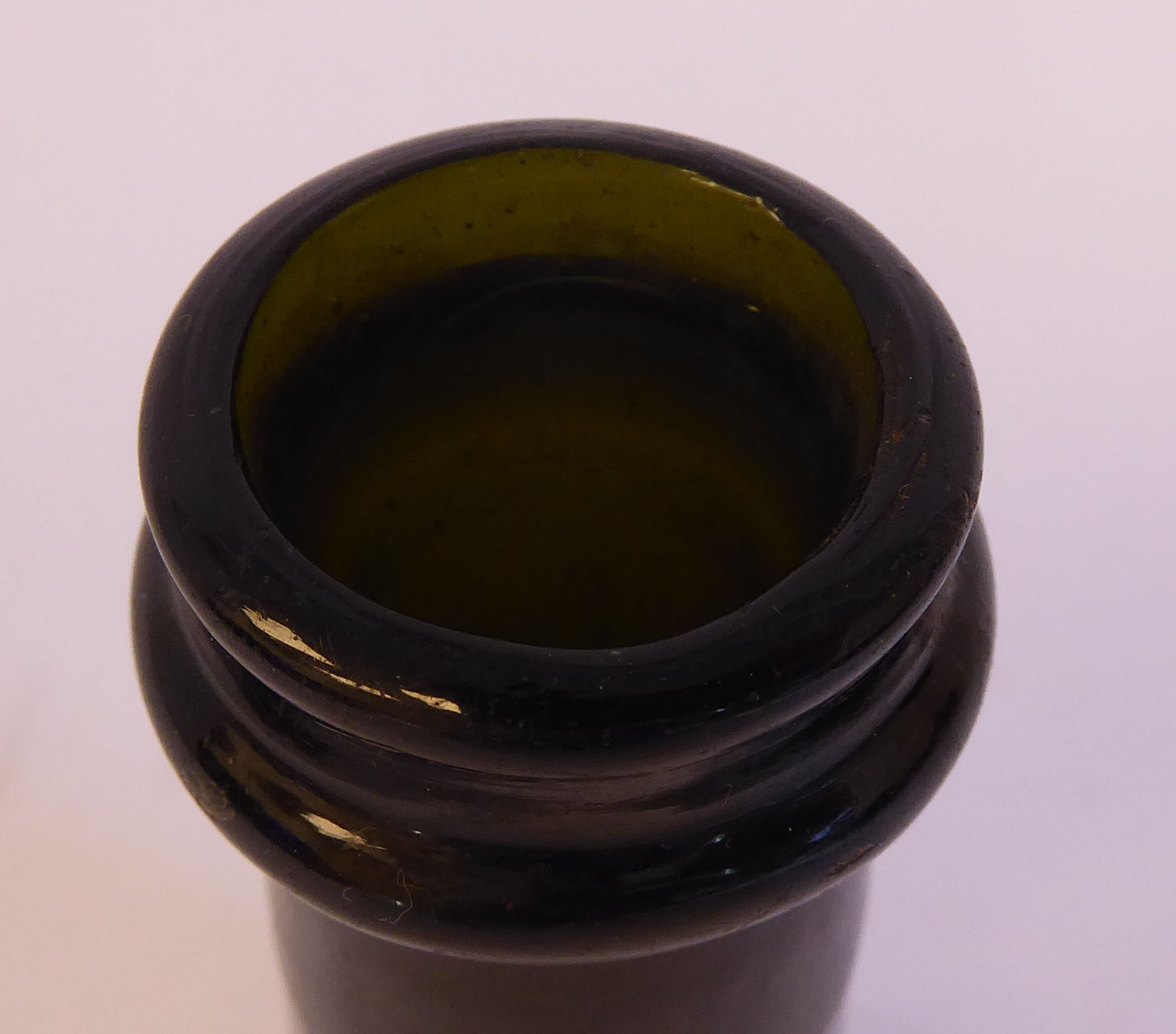 Lot 18 - An 'antique' semi-opaque green glass bottle of tapered cylindrical form with a kick base and