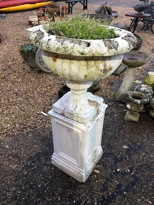 Lot 13 - A pair of weathered stonecrete garden urns raised on square plinths, later painted (2)