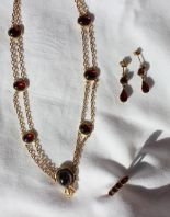 Lot 67 - A yellow metal and garnet set necklace,