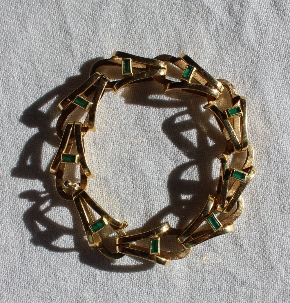 Lot 31 - A yellow metal and emerald set bracelet,