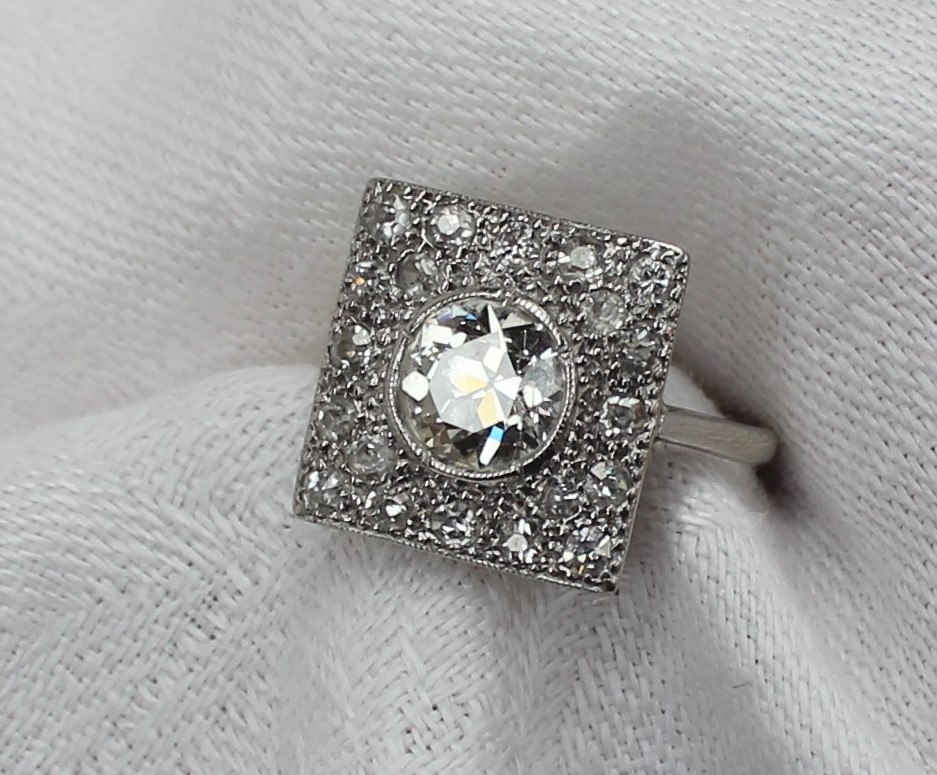 Lot 12 - A diamond dress ring of Art Deco style set with a central round old cut diamond approximately 1.