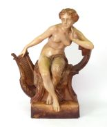 Lot 10 - A Goldscheider figure of a young woman, partially draped, seated on a chair,