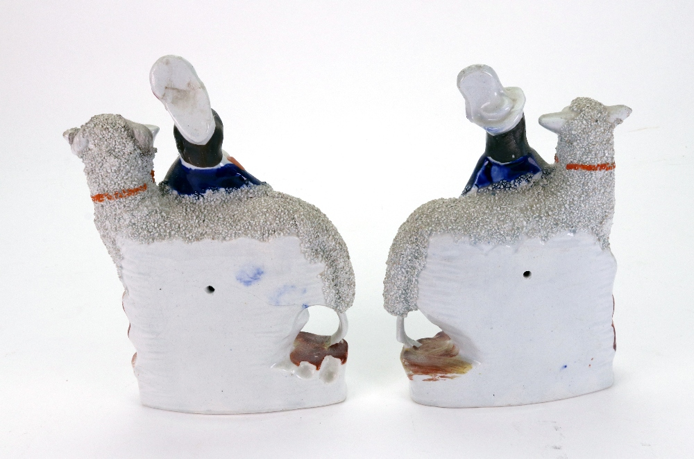 Lot 49 - A pair of Staffordshire highland figures standing before frit decorated sheep, 20.5cm high.