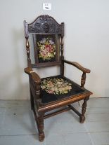Lot 704 - A Victorian carved oak framed armchair upholstered in floral tapestry and with turned supports