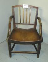 Lot 753 - A 19th century oak elbow chair of small proportions and with solid planked seat and lower stretcher