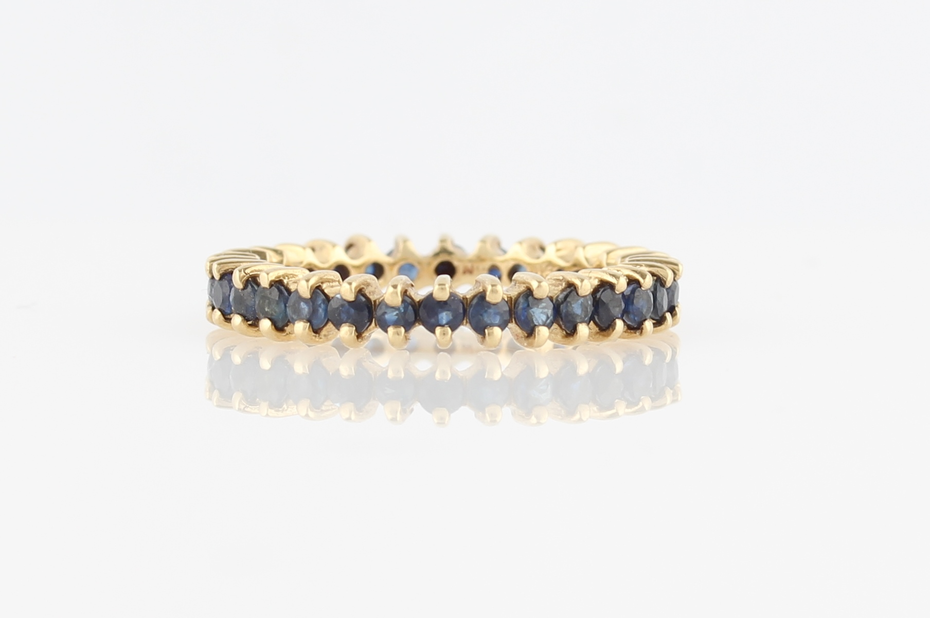 Lot 43 - A sapphire full eternity ring, set with round cut sapphires, stamped 9k, ring size L½.