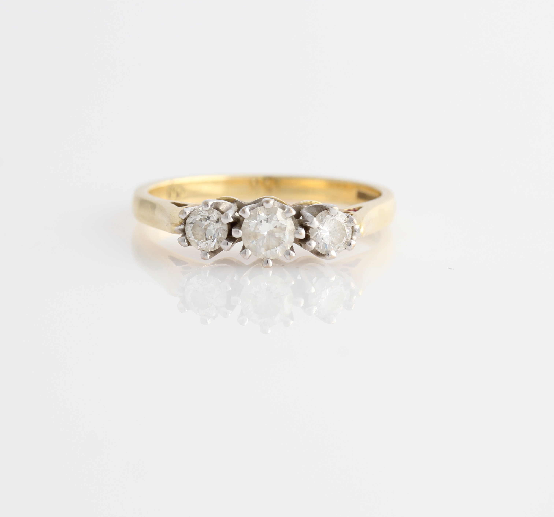 Lot 48 - A hallmarked 18ct yellow gold three stone diamond ring, set with three graduated round brilliant cut