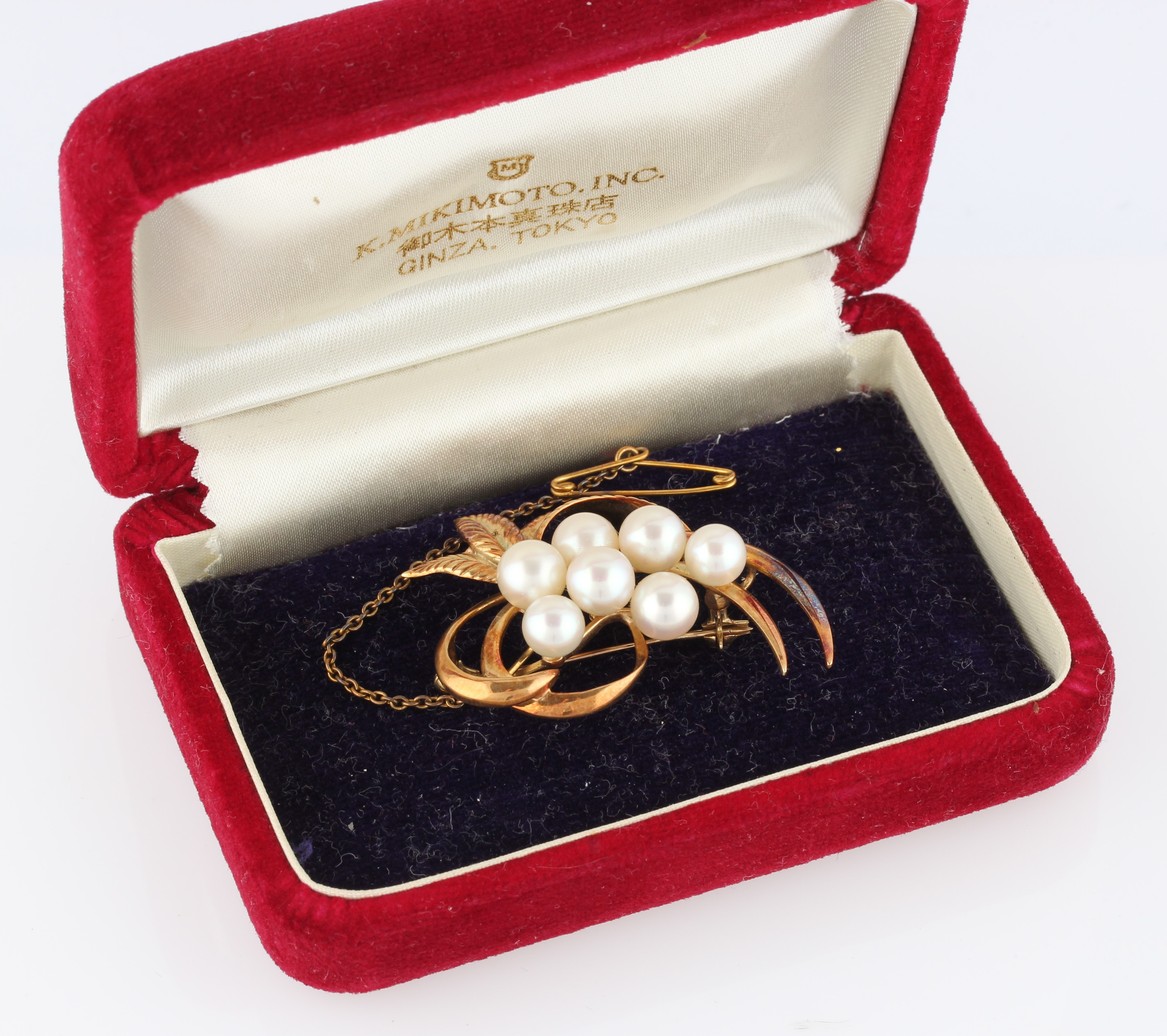 Lot 22 - A Mikimoto pearl brooch, set with seven variously sized pearls, smallest measuring approx. 6mm and