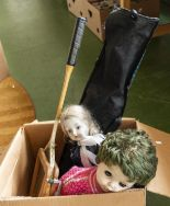 Lot 44 - A box containing dolls and a racquet