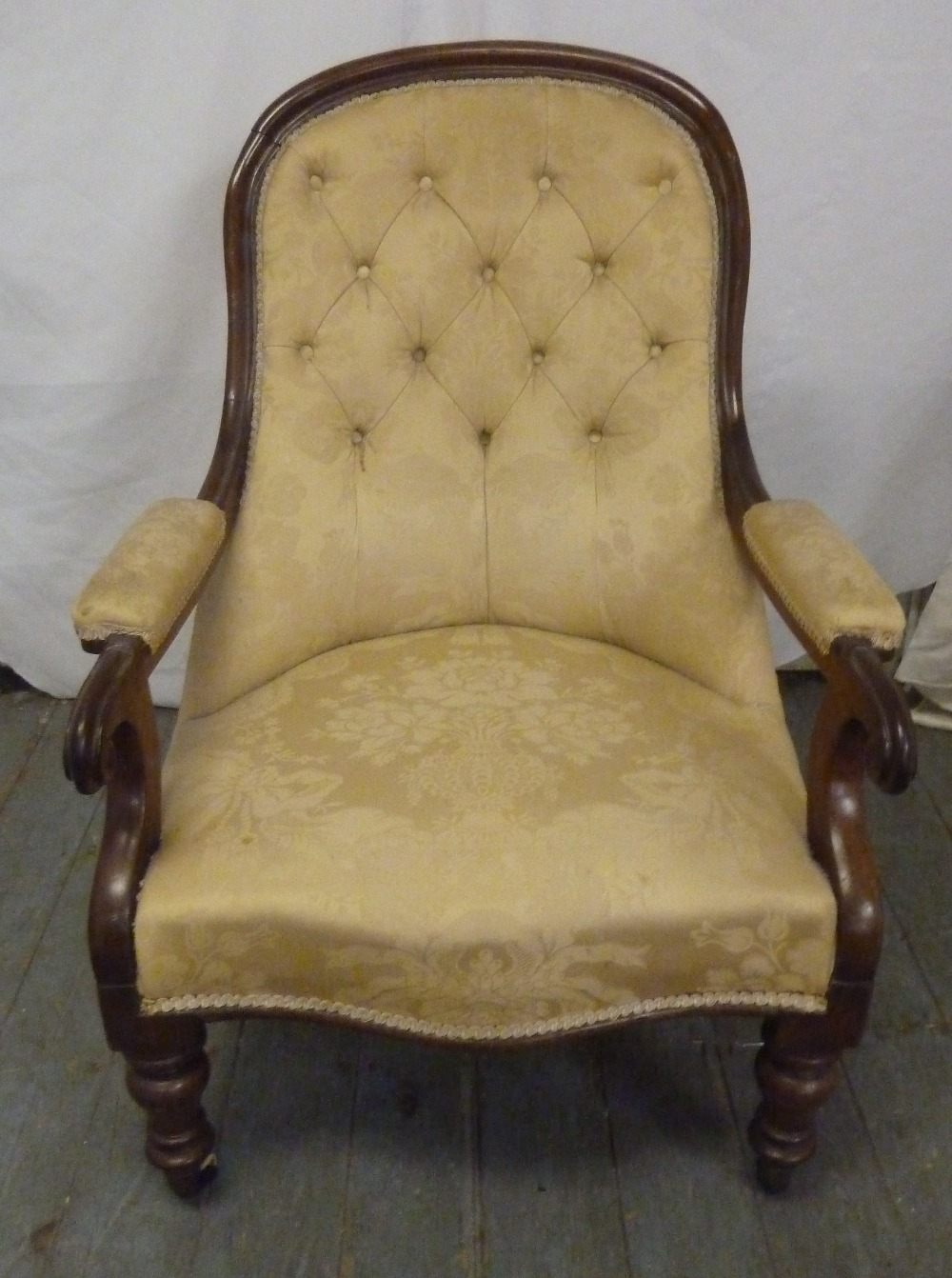 Lot 24 - A Victorian mahogany upholstered armchair on turned legs with original castors
