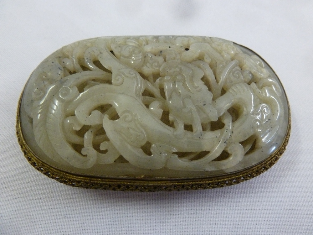 Lot 183 - A Chinese mutton fat jade and gilt metal belt buckle, carved and pierced with leaves and flowers
