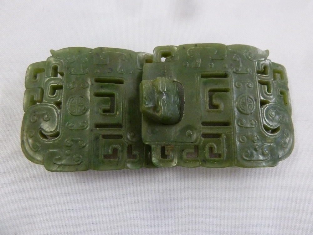 Lot 184 - A Chinese green jade carved and pierced two part belt buckle with stylised mask clasp